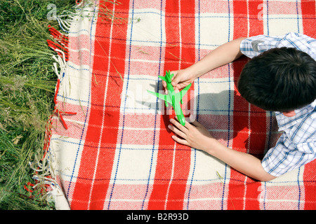 Boy playing with green toy plane - Stockfoto
