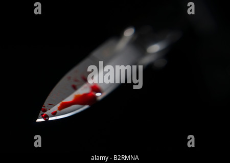 Bloody knife blade against dark background - Stock Photo