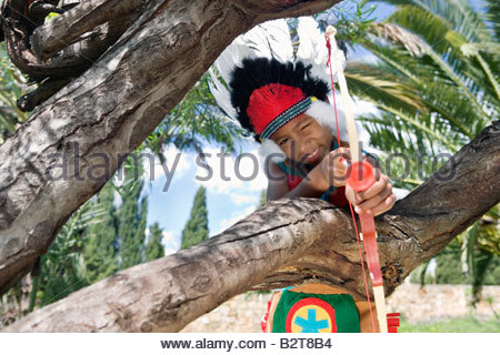 Young boy in indian costume aiming bow and arrow - Stock Photo