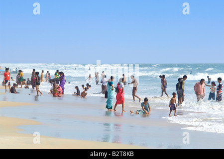 Local Indians enjoying a holiday at the beach on a hot sunny day in Goa. - Stock Photo