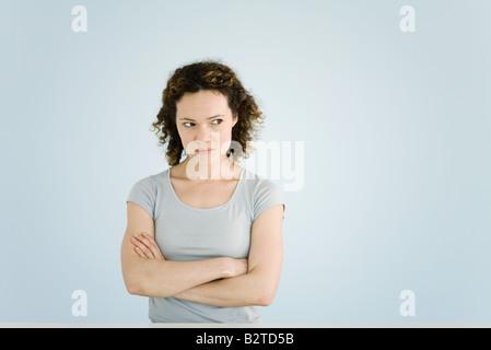 Woman sulking, arms folded, portrait - Stock Photo