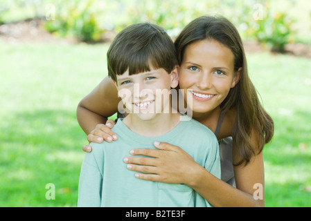 Teen girl standing behind younger brother, hands on shoulder and heart, both smiling at camera - Stock Photo