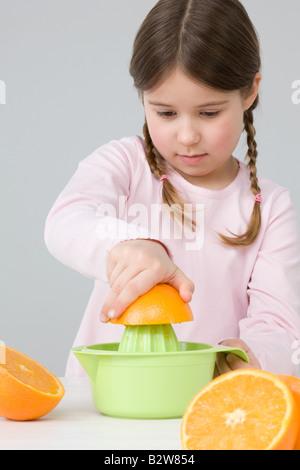 Girl juicing oranges - Stock Photo