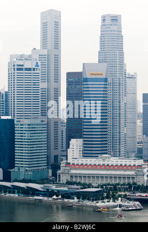 Financial district tower blocks and column front of Fullerton Hotel Singapore Flyer view - Stock Photo