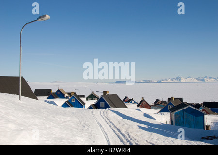 Traditional colourful Greenlandic houses overlooking Scoresbysund fjord in the village of Ittoqqortoormiit, East - Stock Photo