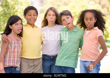 Five young friends standing outdoors making funny faces - Stock Photo