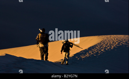 Two photographers walk along a ridge line of the Mesquite Dunes in Death Valley National Park California at sunrise - Stockfoto