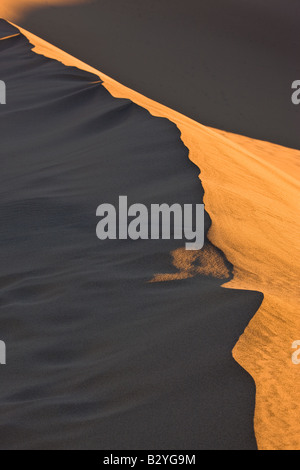 Warm light from the rising sun illuminates a ridge line in the Mesquite Dune Death Valley California - Stockfoto
