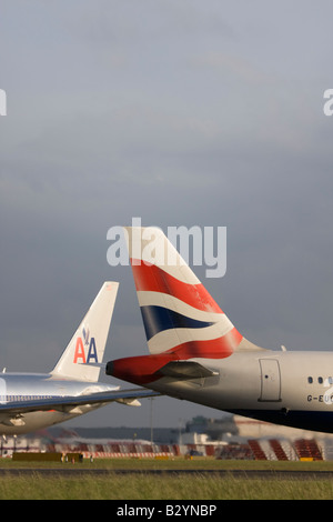The tails of British Airways and American Airlines planes - London Heathrow, United Kingdom - Stock Photo