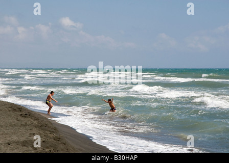 Two young boys playing in the waves at the Seaside resort of Montalto di Marina on the Mediterranean - Stock Photo
