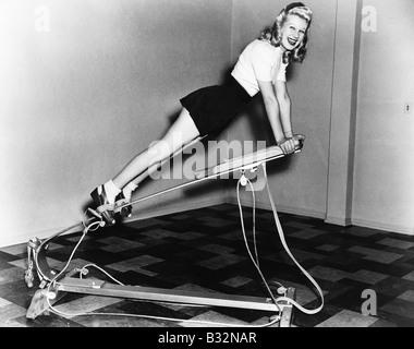 Woman using exercise equipment - Stockfoto