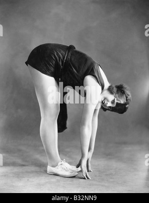 Woman touching toes - Stockfoto