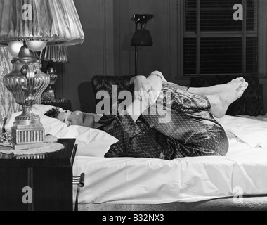 Woman stretching on bed - Stockfoto