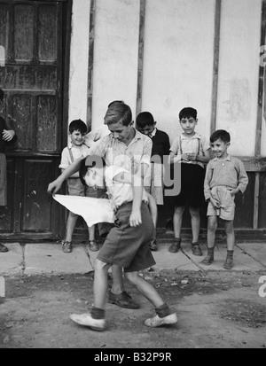 Kids playing bullfighting game in street - Stock Photo