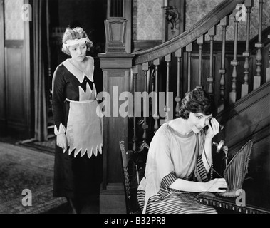 Maid eavesdropping on womans telephone call - Stock Photo