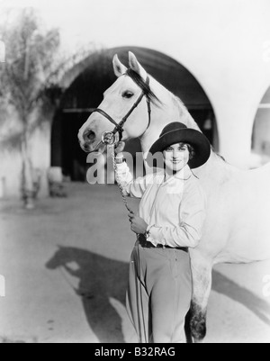 Young woman standing proudly with her horse - Stock Photo