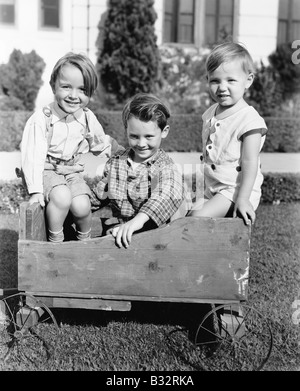 Three boys sitting in a push cart and smiling - Stock Photo