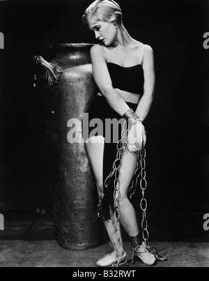 Woman chained in front of a big vase - Stock Photo