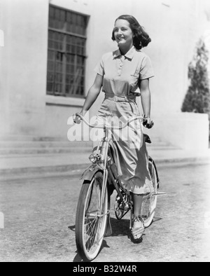 Young woman riding her bike - Stock Photo