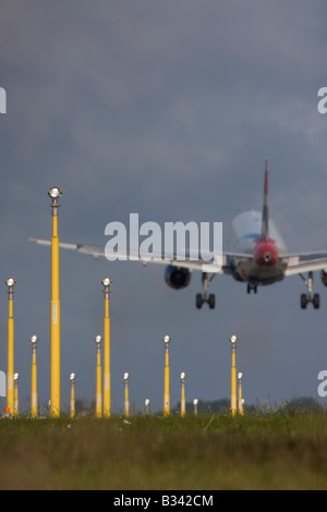 Commercial aeroplane on short final approach to London Heathrow Airport with landing lights in the foreground. - Stock Photo