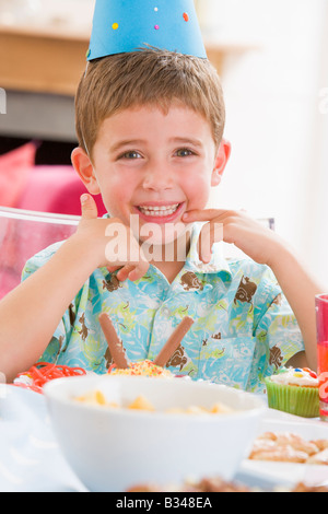 Young boy at party sitting at table with food smiling - Stockfoto