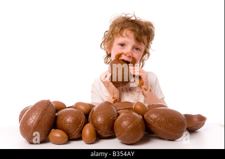 young boy with large pile of easter eggs eating egg - Stockfoto