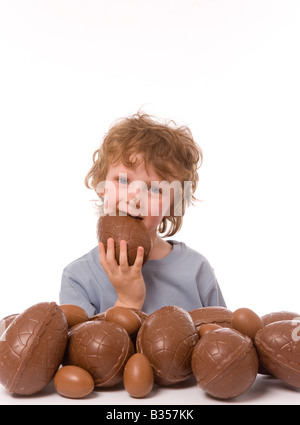 young boy with large pile of easter eggs eating egg with chocolate on face. - Stockfoto