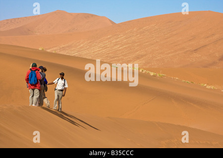 Visitors hike among sand dunes in Sossusvlei Namibia Africa - Stock Photo