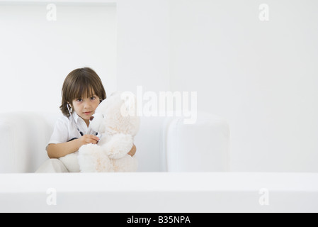 Little boy playing doctor with teddy bear, using stethoscope - Stock Photo
