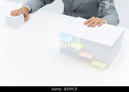 Stacks of paper with adhesive notes dividing them, man putting one hand on each stack - Stockfoto