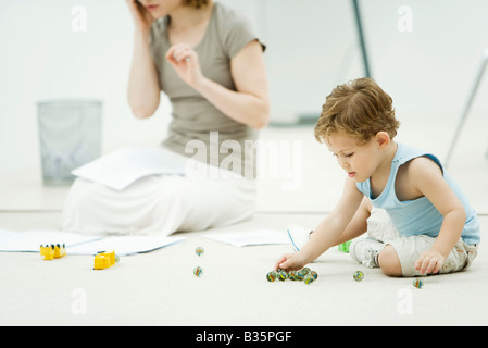 Little boy sitting on the ground, playing marbles, mother surrounded by paperwork in background - Stockfoto