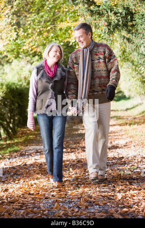 Couple outdoors walking on path in park holding hands and smiling (selective focus) - Stock Photo