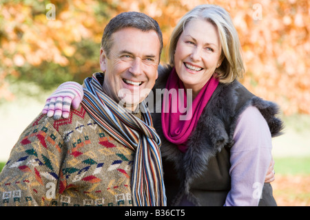 Couple outdoors embracing and smiling (selective focus) - Stock Photo