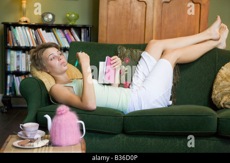 Young woman lying on sofa at home writing in her diary - Stock Photo