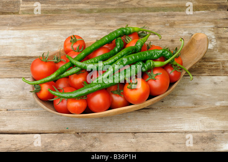 Freshly picked home grown organic Tomatoes Chillies in a rustic wooden bowl - Stock Photo