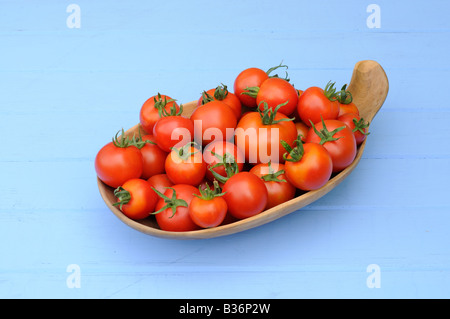 Freshly picked home grown organic Tomatoes in a rustic wooden bowl - Stock Photo