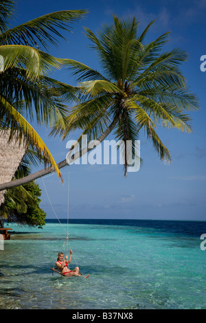 Girl swinging on rope swing on South Ari Atoll in Maldives near India - Stockfoto