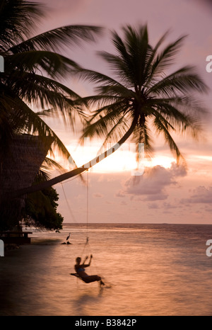 Girl swinging on rope swing at sunset on South Ari Atoll in Maldives near India - Stockfoto