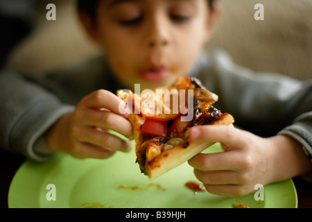 Homemade Pizza Six year old boy tucks into a slice of his mother s home cooking Mixed race Indian ethnic - Stock Photo