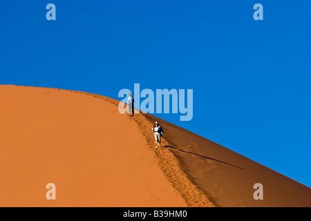 Climbing Dune 45 in the Namib-Naukluft National Park, Namibia - Stockfoto