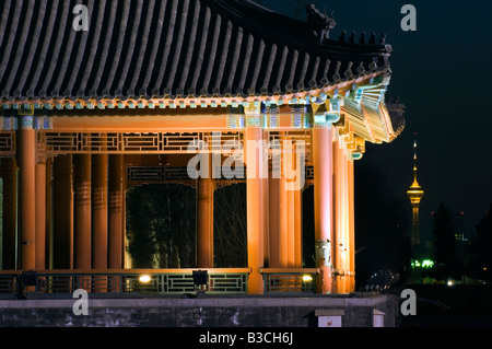China, Beijing. Forbidden City Palace Museum illuminated with the CCTV tower in the distance, UNESCO World Heritage - Stock Photo