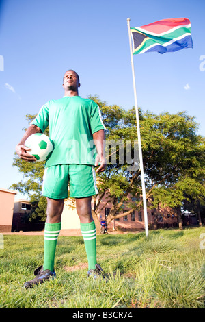 Monkeyapple  aFRIKA Collection  Great Stock ! Soccer player posing with ball under South African flag - Stockfoto
