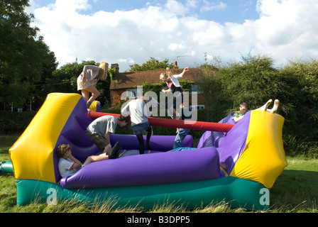 Teenagers playing on an inflatable bouncy castle outdoor party - Stock Photo