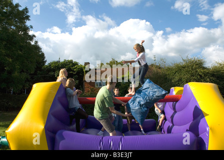 Teenagers playing on an inflatable bouncy castle outdoor birthday party - Stock Photo