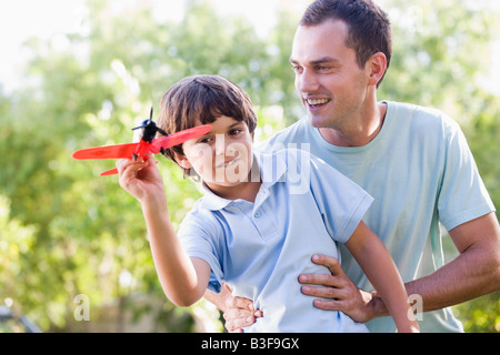 Man and young boy outdoors playing with toy airplane smiling - Stockfoto