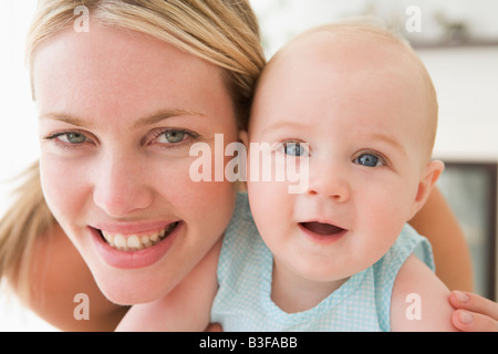 Mother in living room with baby smiling - Stock Photo