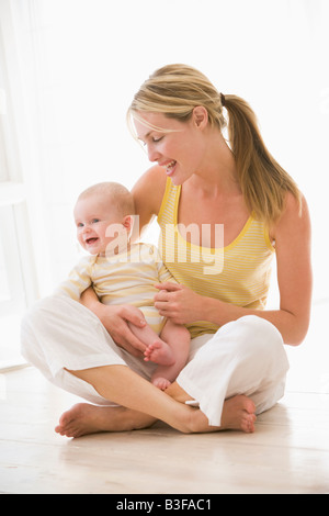 Mother and baby sitting indoors smiling - Stock Photo