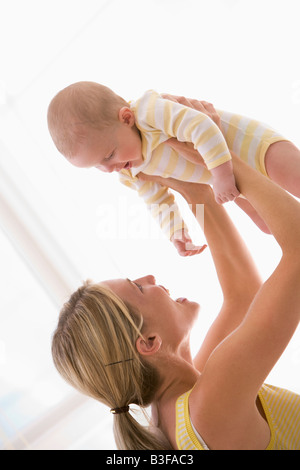 Mother holding baby indoors smiling - Stock Photo
