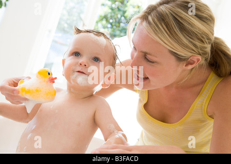 Mother giving baby bubble bath smiling - Stock Photo