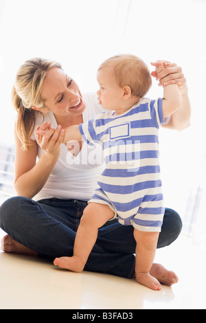 Mother and baby indoors playing and smiling - Stockfoto